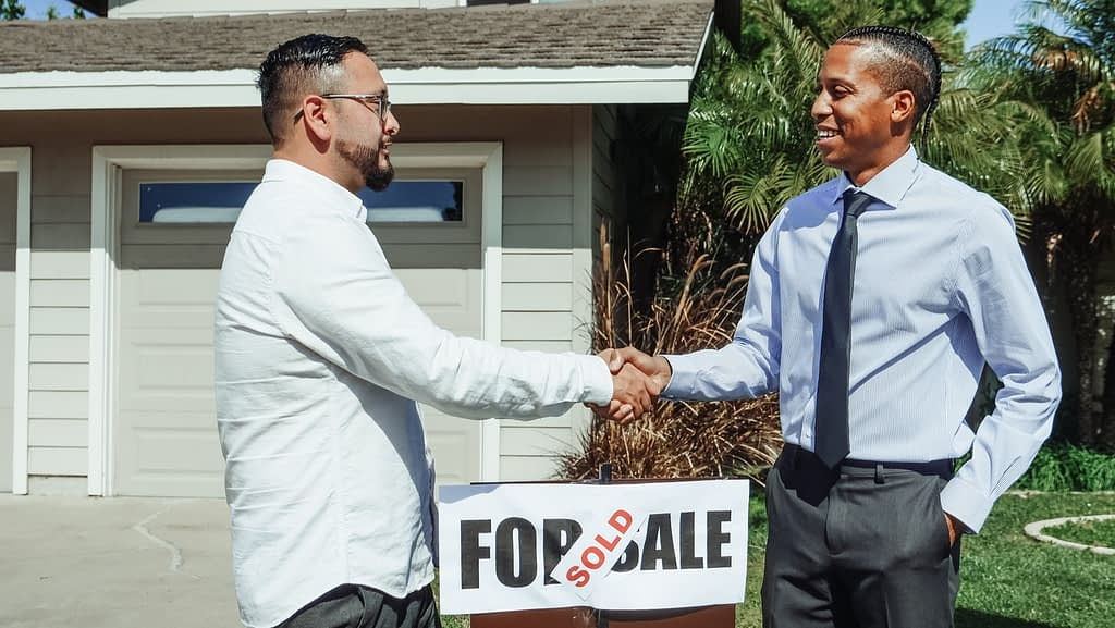 An investor and realtor shaking hands in front of a sold property
